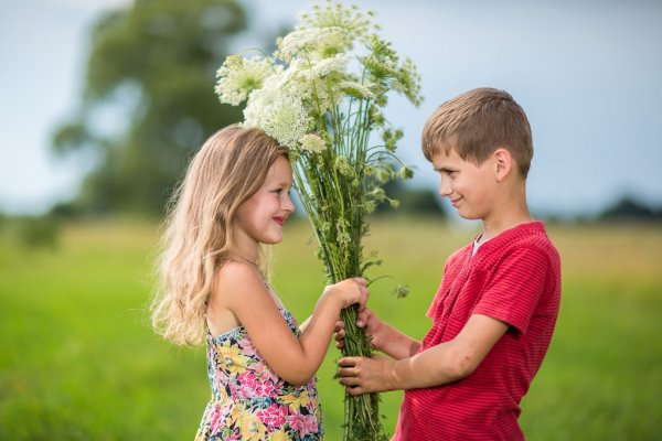Spring. Boy gives girl a bouquet of flowers . — стоковое фото